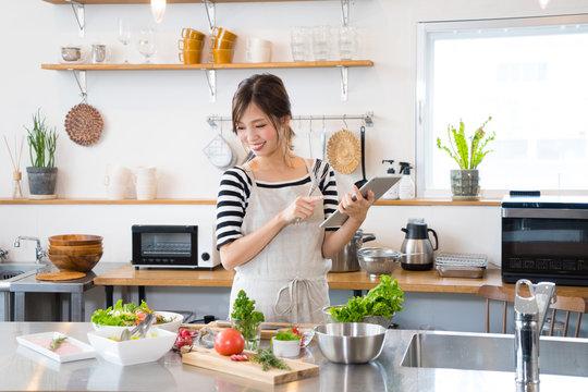タブレットを見ながら料理を作る若い女性