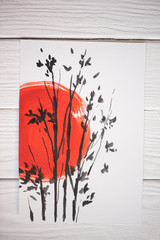 Top view of paper with Japanese painting with red sun and branches on wooden background