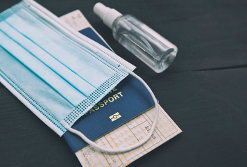The ticket inside the passport and the medical mask with sanitizer as an essential thing in travel...