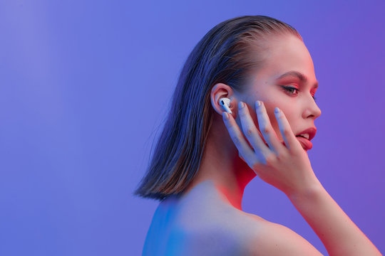 A beautiful young girl in wireless headphones listens to song with a good mood. bright colorful music poster.