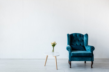comfortable armchair near tulips on coffee table in living room
