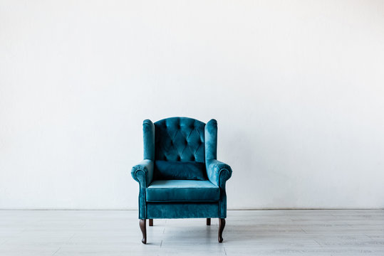 comfortable armchair near white wall in living room