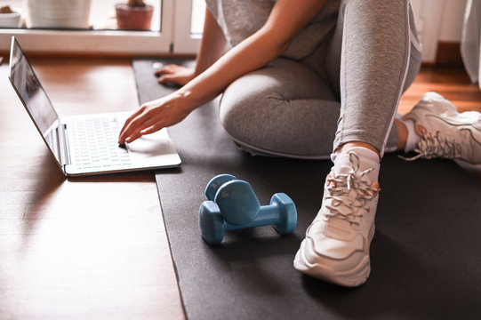 Training, Fitness At Home. Sporty man doing yoga plank while watching online tutorial on laptop, exercising in living room. woman multitasking remote work indoors lifting weights dumbbells