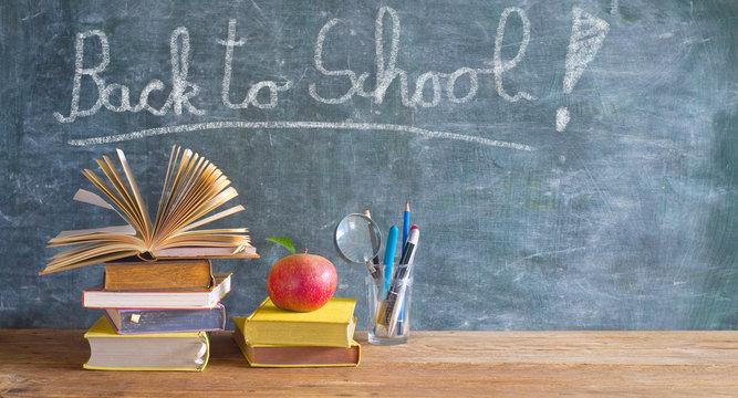 Back to school after the coronavirus pandemic lockdown, education supplies, books, pens, message on blackboard
