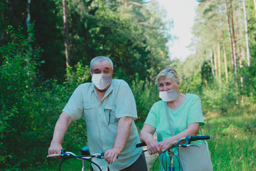 active senior couple maintaining social distancing on bike ride in nature
