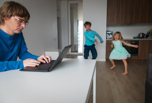 family stay home, father working remotely while kids dance and have fun