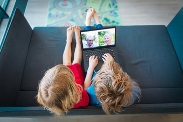 little boy and girl talk with grandparents through conference call, social distancing during covid