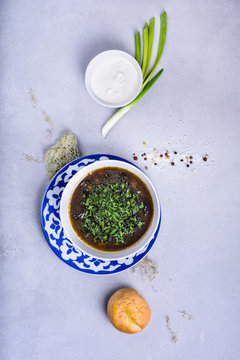 Soup in a bowl, with herbs and sour cream. Top view, copy space.