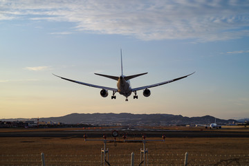 Airplane landing to airport runway in sunset light 旅客機・夕暮れの着陸