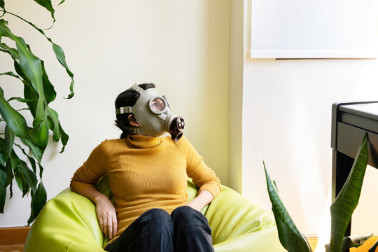 Horizontal view of woman with gas mask surrounded with plants looking through the window. Conceptual idea of greenhouse effect in ecosystem. Quarantine at home and covid 19 coronavirus concept.