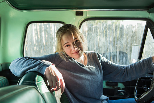 portrait of smiling 14 year old girl behind the wheel of a 1970's pick up truck