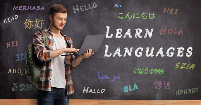 Male student wiht a laptop and standing in front of a blackboard with text learn languages