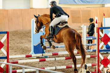 equestrianism on horse jump over obstacle in competition Papier Peint