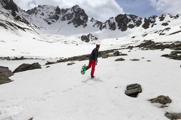 Wall Mural - Happy hiker in green snowshoes with raised leg