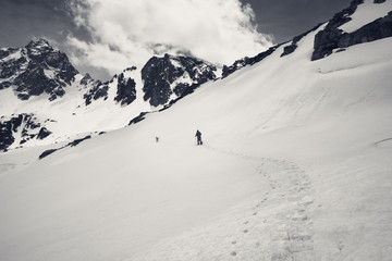 Wall Mural - Hiker in snowshoes with dog in high snowy mountain at gray day