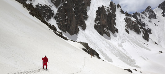 Wall Mural - Mountains with avalanche traces, sunlit cloudy sky, hiker and dog on snowy slope