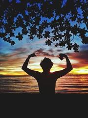 Fototapeta Rear View Of Silhouette Man Flexing Muscles While Standing At Beach Against Sky During Sunset obraz