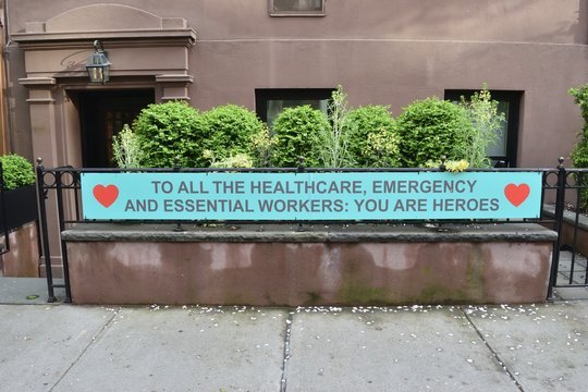 Sign on a fence railing reading To All The Healthcare, Emergency And Essential Workers: You Are Heroes with two red heart symbols and a brownstone and green shrubs, May 1, 2020, in New York.