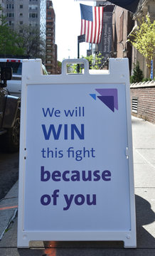White A-frame sign reading We Will Win This Fight Because Of You on a city sidewalk with American flag in the background, May 7, 2020, in New York.