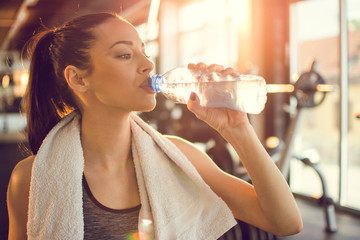 Closeup portrait of beautiful young fit woman drinking water during traning in the gym.