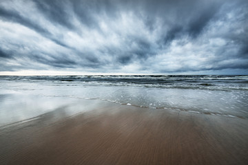 Storm clouds above the North sea in winter, long exposure. Dramatic sky, waves and water splashes. Dark seascape. Netherlands