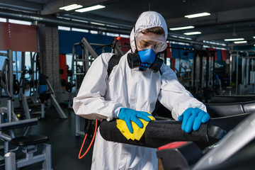 Poster de jardin Fitness professional disinfector personal protective equipment ppe suit, gloves, mask, cleaning gym space with pressurized spray disinfectant water to remove covid-19 coronavirus