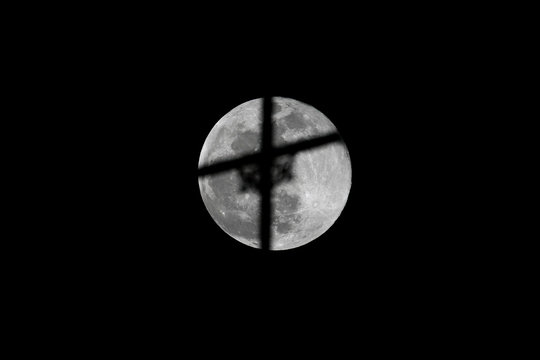 The full moon, also known as the Supermoon or Flower Moon, rises behind the silhouetted cross of the St. Andrews Church, as the outbreak of the coronavirus disease (COVID-19) continues, in Karachi