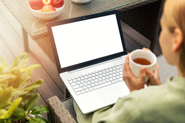 woman drinking tea and using laptop on a outdoor terrace, blank screen copy space