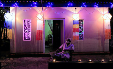 A man wearing a face mask sits in front of his house, decorated with lights and lanterns, on the Vesak Day, which is celebrated in Sri Lanka on May 7th and 8th to commemorate the birth, enlightenment and death of Buddha, during the curfew amid concerns abo