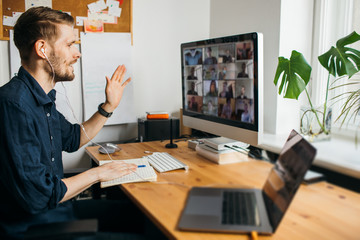 Young man having video conferencing call via computer. Working remotely managing team virtual call  Stay at home and work from home. Virtual House party Home office computer desk.