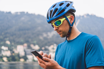 The theme of tourism and travel in Italy. A male cyclist uses a phone on the shore of Lake Como. Tourist guy in a helmet with a bicycle on the shore of a mountain lake in northern Italy