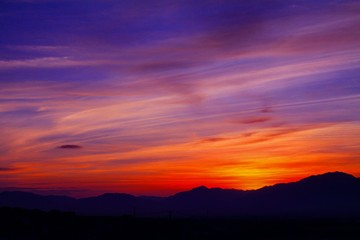 Foto auf AluDibond Hochrote Scenic View Of Silhouette Mountains Against Orange Sky