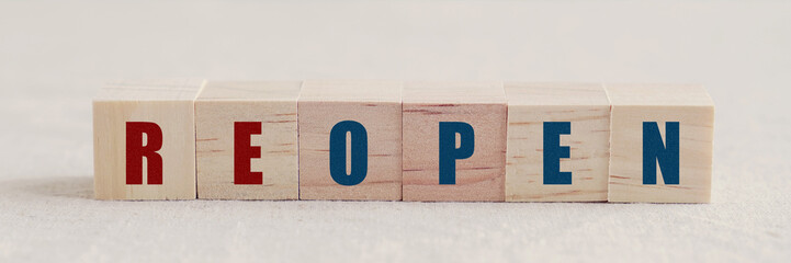 Wooden blocks with REOPEN word, business reopening plan post covid-19 coronavirus pandemic concept