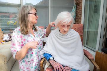 Elderly woman has hair cut by her carer during Corona virus lockdown at home.
