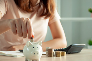 Women are putting coins in a piggy bank for a business that grows for profit and saving money for the future. planning for retirement concept