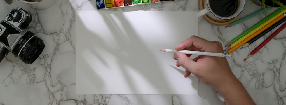 Overhead shot of male artist drawing on sketch paper with painting tools