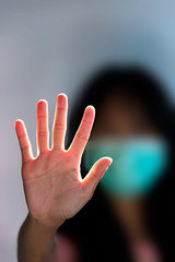 Girl wearing mask for protect blur (shallow depth of field) show stop hands gesture for stop corona virus outbreak