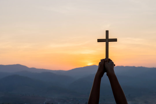 Christian, Christianity, Religion copy space background. Human praying and holding christian cross for worshipping God at sunset background.