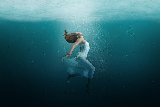 Dancer underwater in a state of peaceful levitation as she dances.
