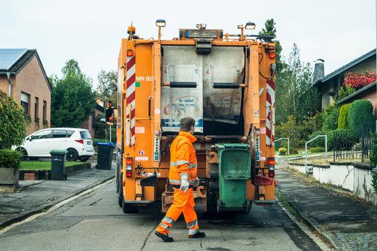 Garbage removal at work - garbage collector picks up the garbage