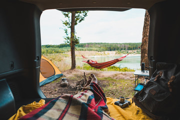 Foto op Canvas Kamperen person view couple resting at camping woman laying in hammock with beautiful view of forest lake