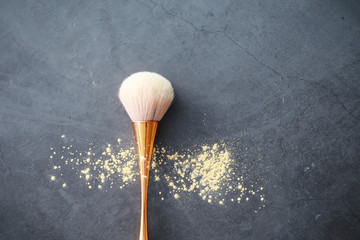 Powder and makeup brush. Brown powder on the background. Makeup products. Style concept.