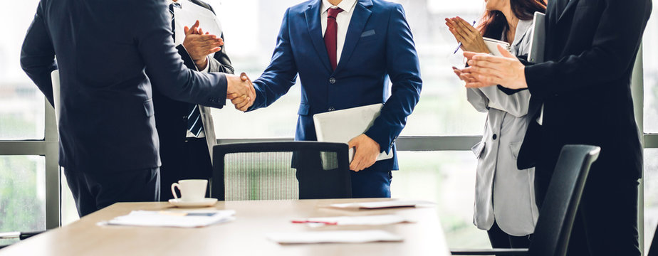 Image two business partners in elegant suit successful handshake together in front of group of casual business clapping hands in modern office.Partnership approval and thanks gesture concept