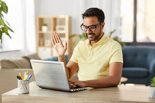 technology, remote job and lifestyle concept - happy indian man in glasses with laptop computer having video chat and waving hand at home office