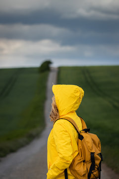 Rain is coming. Woman hiking on road and looking at cloudy sky. Backpacker wearing yellow waterproof jacket with hood