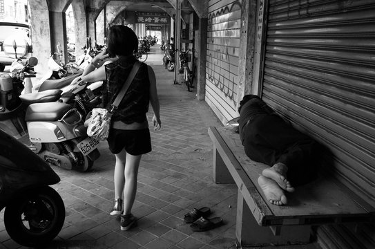Young Woman Walking By Homeless Man