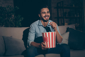 Portrait of his he nice attractive glad cheerful brunet guy spending holiday sitting on divan watching show eating corn at industrial loft style interior dark room house flat apartment indoors
