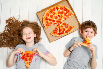 Children holding a slices of pizza lying on the wooden floor.