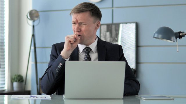 Sick Businessman Coughing at Work