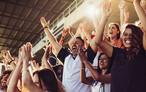 Crowd of sports fans cheering during a match in stadium